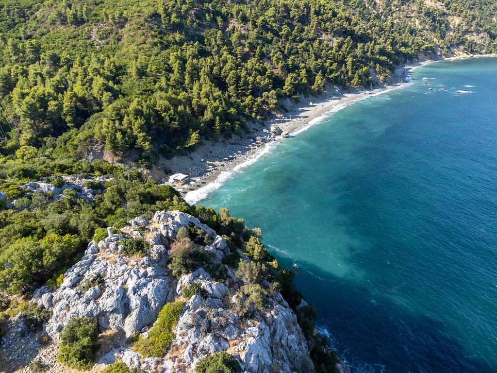Velanio Strand auf Skopelos mit dunklem Sand und türkisem Wasser. Luftbild