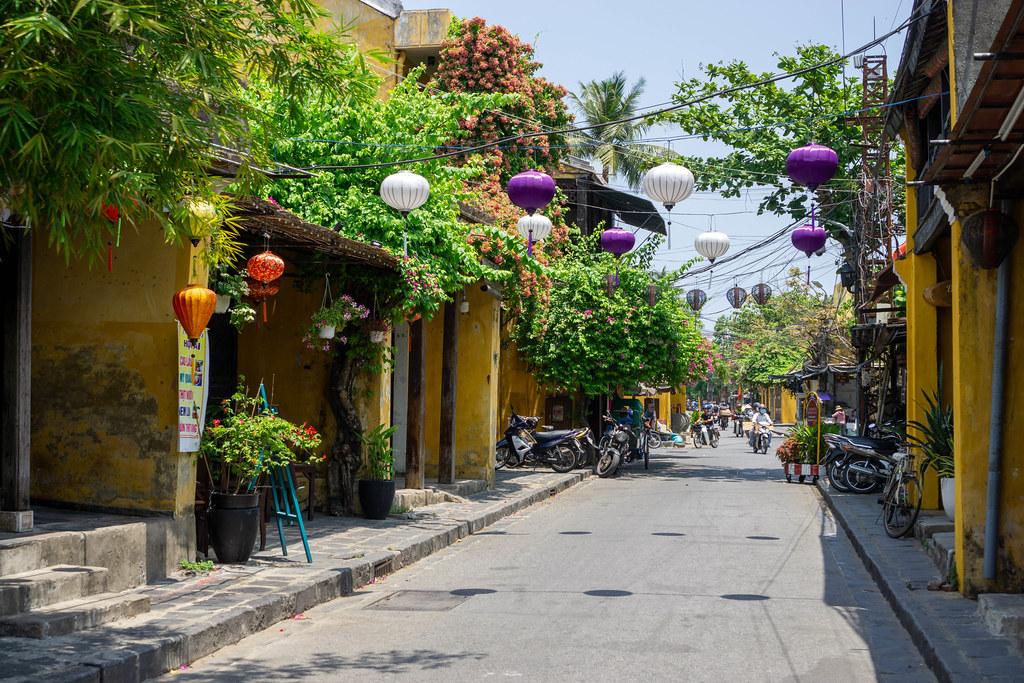 Verschiedene Hängende Lampions, Pflanzen und Bäume neben gelben Gebäuden in der Altstadt von Hoi An, Vietnam