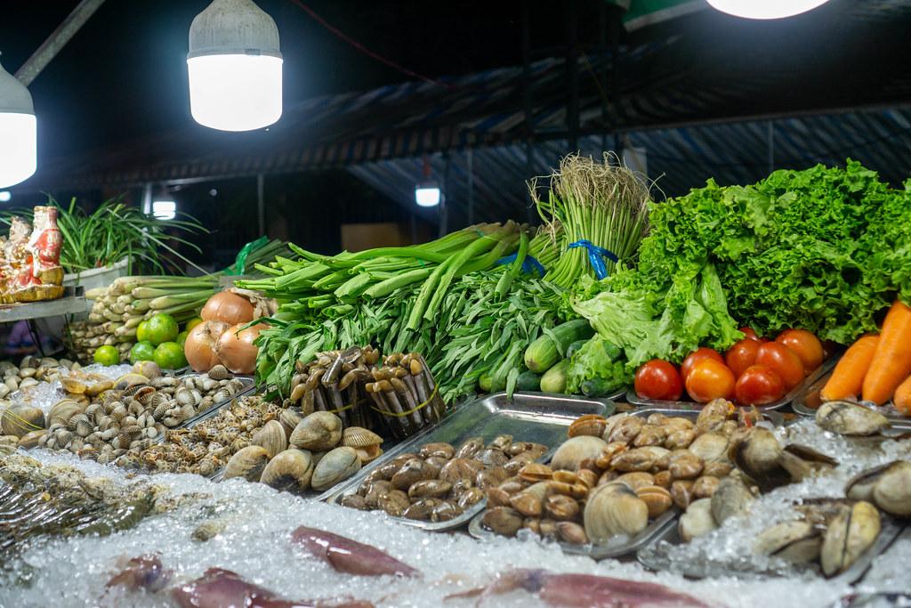 Verschiedene Meeresfrüchte wie Tintenfisch, Garnelen und Muscheln auf Eiswürfeln mit frischem Gemüse im Hintergrund bei einer Straßenküche auf dem Nachtmarkt in Can Tho, Vietnam