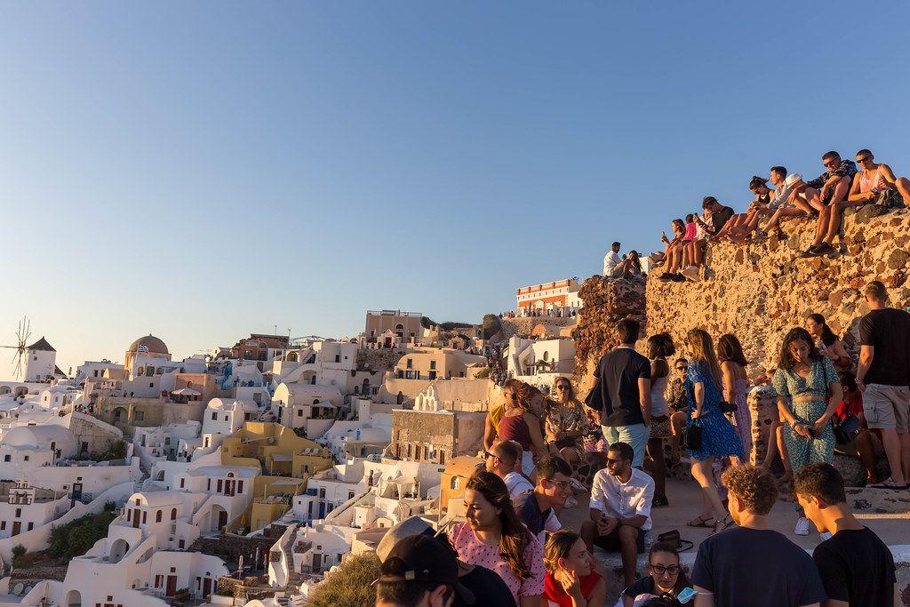 Viele Touristen besuchen am Abend den besten Fotospot für den Sonnenuntergang in Oia, Santorin