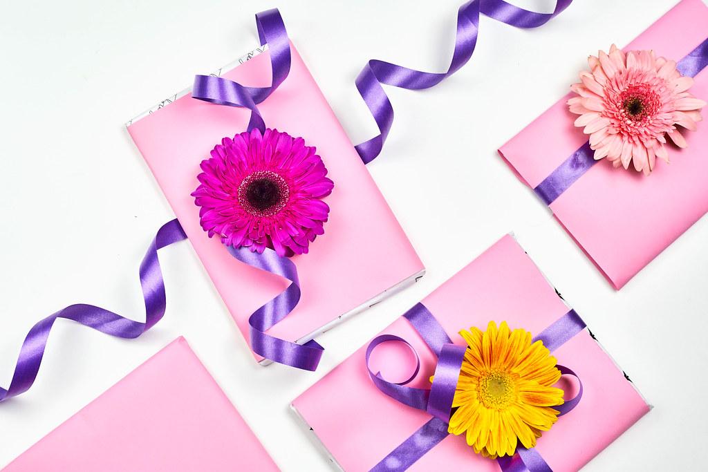 Vier Geschenke in Rosa verpackt und mit lila Schleife und bunten Blumen verziert. Weißer Hintergrund
