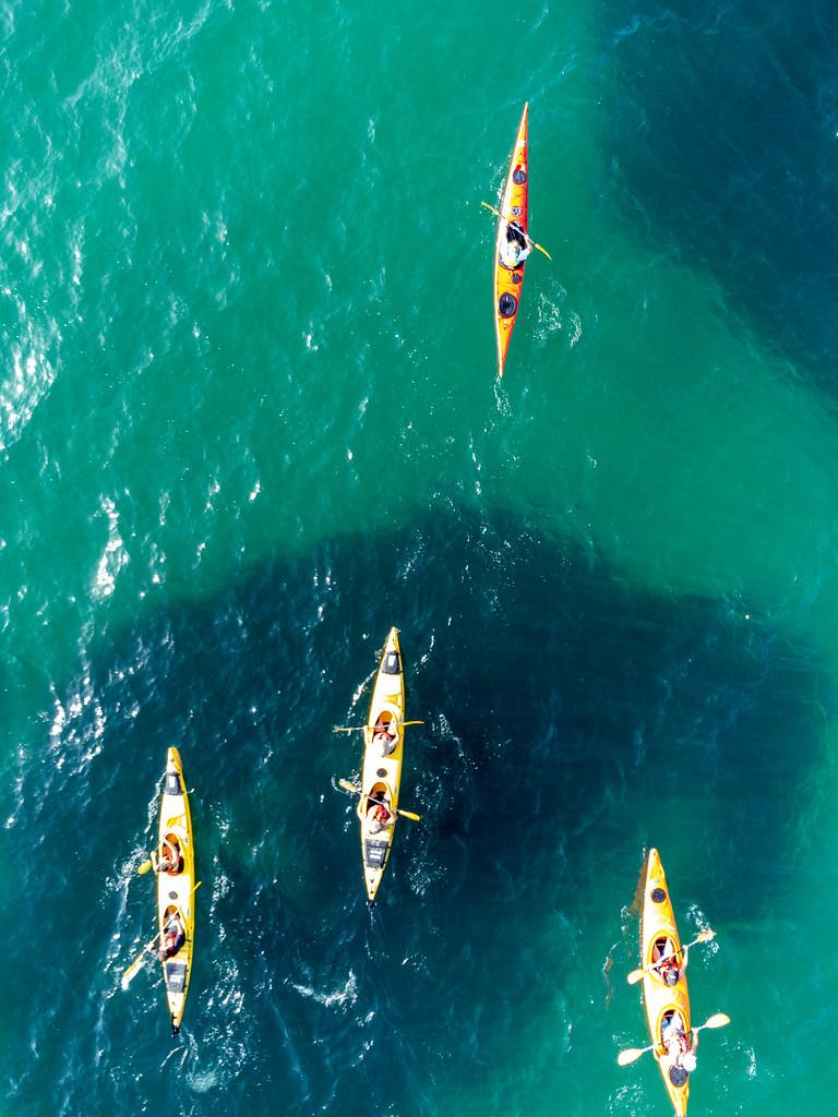 Vier Kajaks im türkisen Wasser vor Kastani Strand. Drohnenaufnahme von aktivem Urlaub auf Skopelos