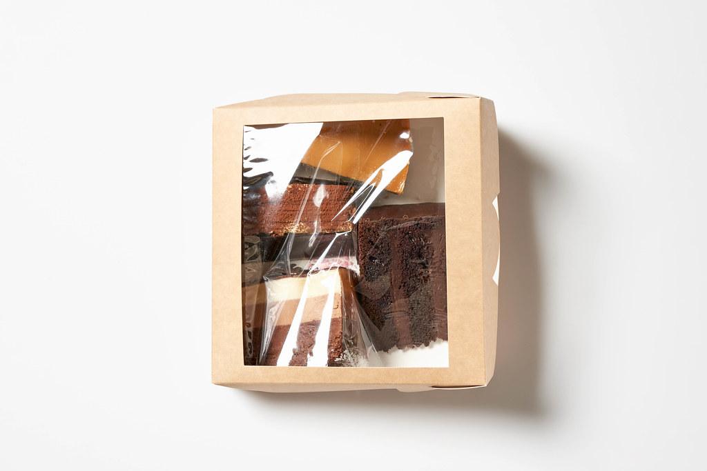 Vier verschiedene Tortenstücke in transparenter Verpackung-Box vor weißem Hintergrund
