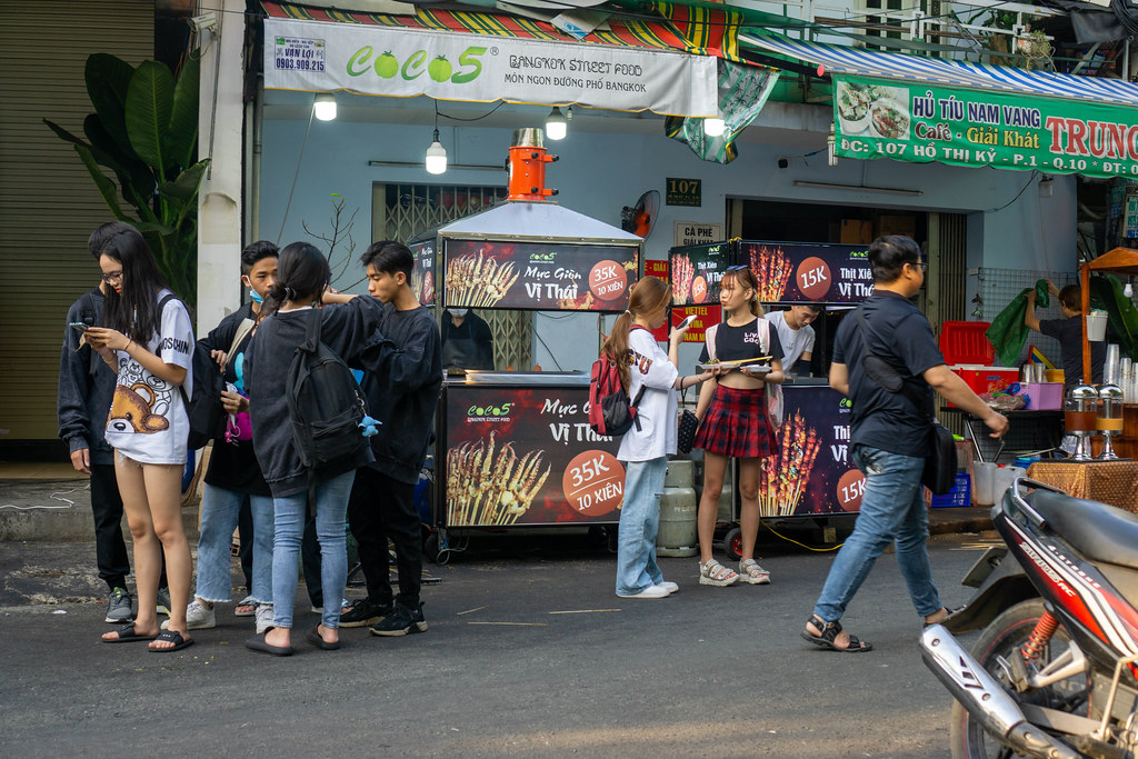 Vietnamese High School Students standing around Street Food Carts at Ho Thi Ky Flower Market in Ho Chi Minh City, Vietnam