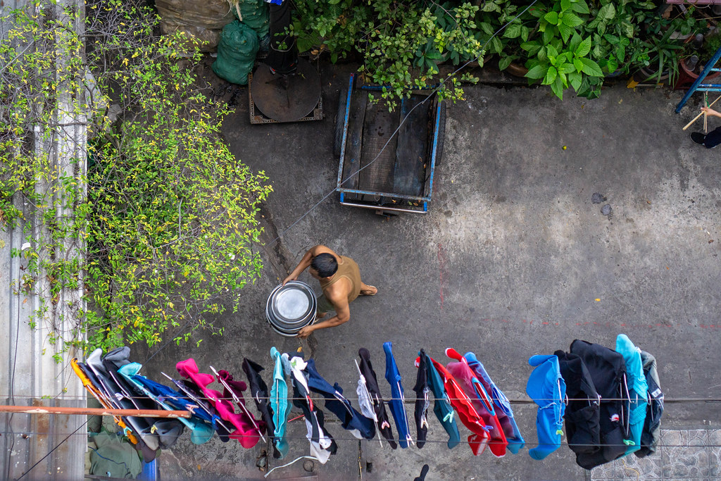 Vietnamese Man carrying Large Bowls inside an Alley with Laundry hanging on a Clothes Line in a Local Area in Saigon, Vietnam