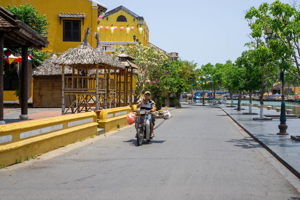 Vietnamese Man on a Motorbike with Durian Fruits in an empty Ancient Town with Yellow Buildings and Lanterns in Hoi An, Vietnam