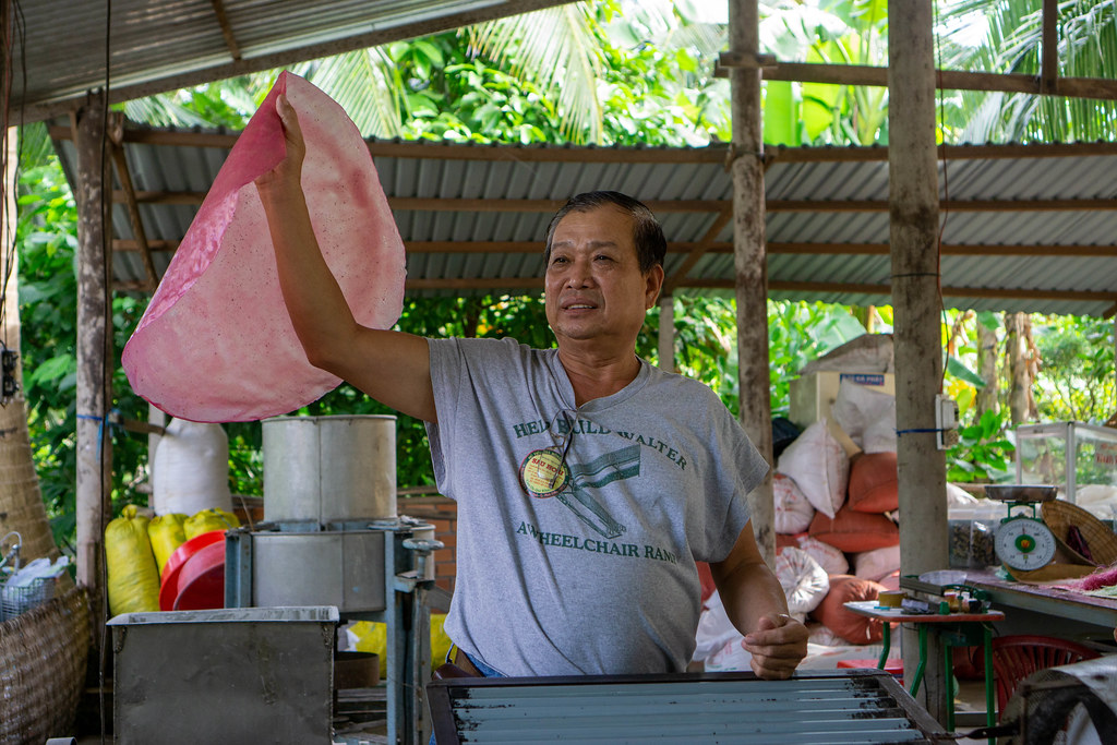 Vietnamese Man showing how to make Handmade Vermicelli from Rice Paper at a Workshop in the Mekong Delta, Vietnam