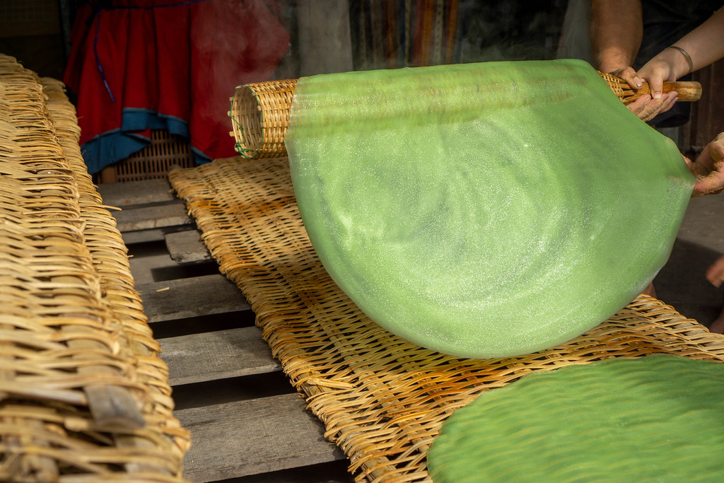 Vietnamese Vegetable Handmade Rice Paper is being placed on a Bamboo Rack to dry in the Sun at a Local Workshop in the Mekong Delta in Vietnam