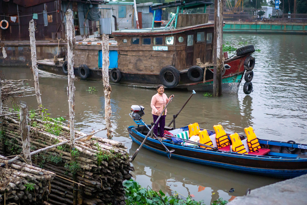 Vietnamese Woman picking up Tourists for a Cai Rang Floating Market Private Tour with a Wooden Motorboat with Life Vests in Can Tho, Vietnam