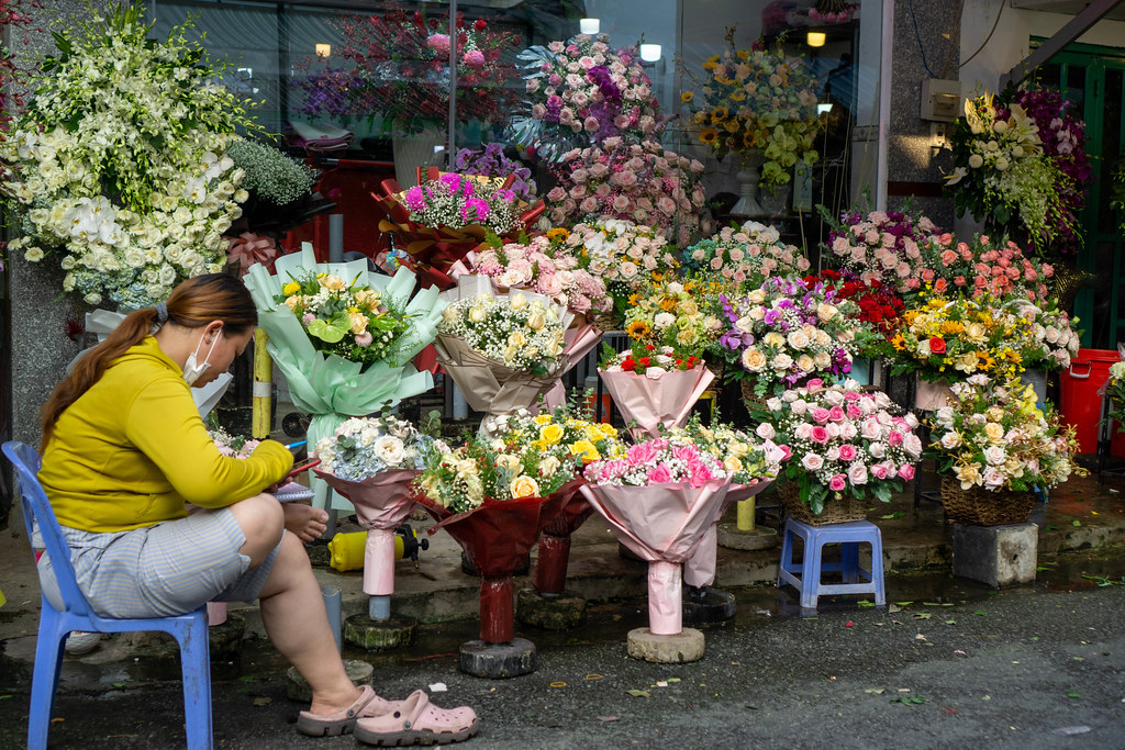 Vietnamese Woman selling colorful Flower Bouquets with Roses, Sunflowers and other kinds of Flowers at the Ho Thi Ky Street Flower Market in Ho Chi Minh City, Vietnam