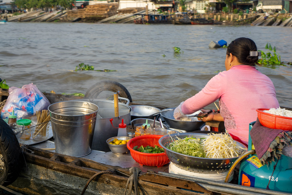 Vietnamese Woman selling Hu Tieu Soup from a Noodle Soup Kitchen on a Boat at Cai Rang Floating Market in Can Tho, Vietnam