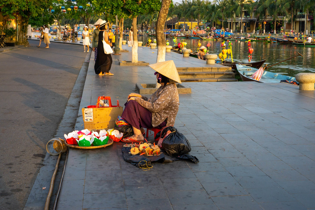 Vietnamese Woman with a Conical Hat selling Floating Lantern Candles on the Pedestrian Street along the Thu Bon River in Hoi An, Vietnam