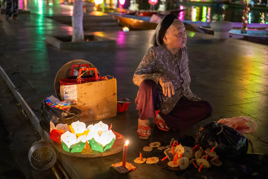 Vietnamese Women sitting on the Sidewalk selling Floating Paper Lanterns with Candles at Night to release in Thu Bon River in Hoi An, Vietnam