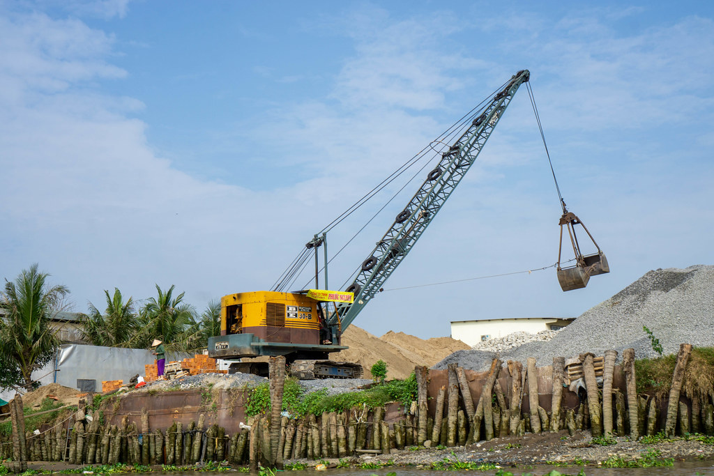 Vietnamese Worker next to a Excavator Crane on a Building Construction Site with Pebbles and Sand in Can Tho, Vietnam