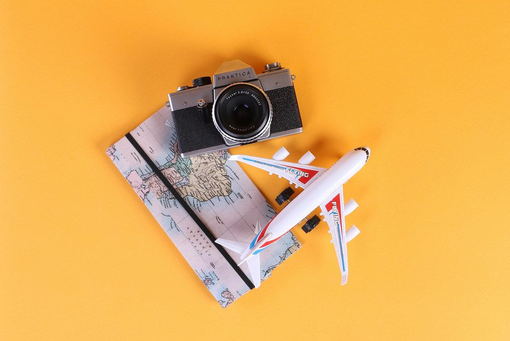 Vintage camera, map and airplane on orange background