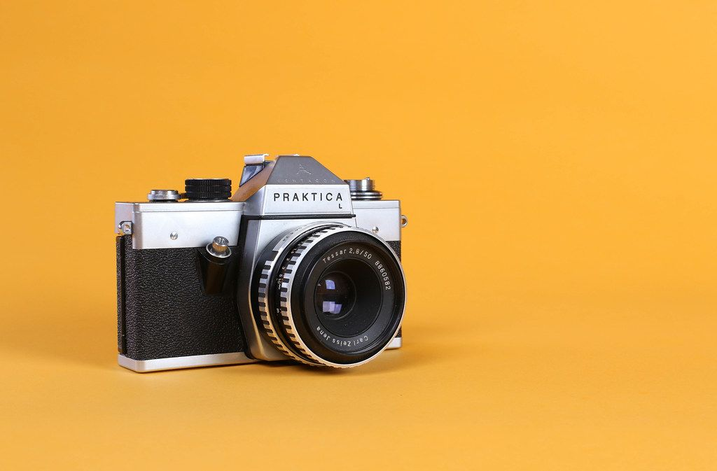 Vintage camera on orange background