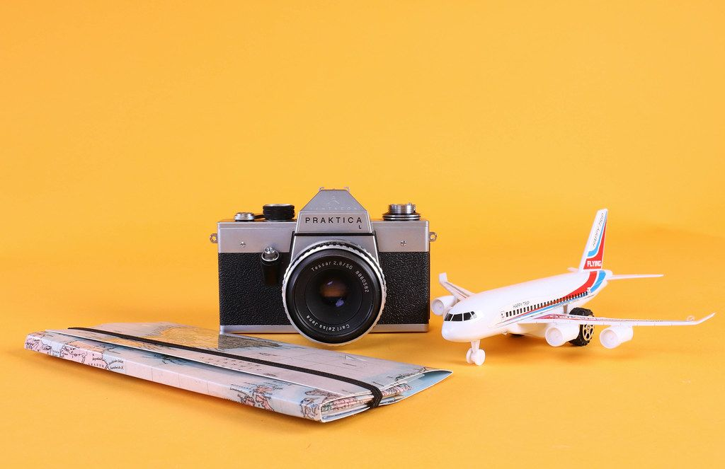 Vintage camera with map and airplane on orange background