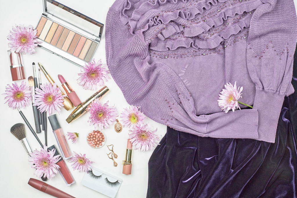Violet colored light sweater and skirt with make-up tools and spring flowers
