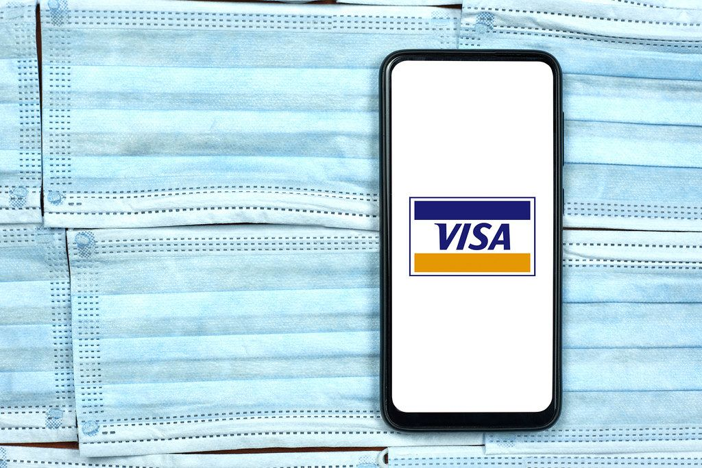 Visa company logo on smartphone screen over the face masks. Global company during coronavirus crisis