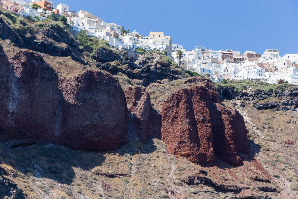 Volcanic rock formations below the white village of Oia on the Greek island Santorini