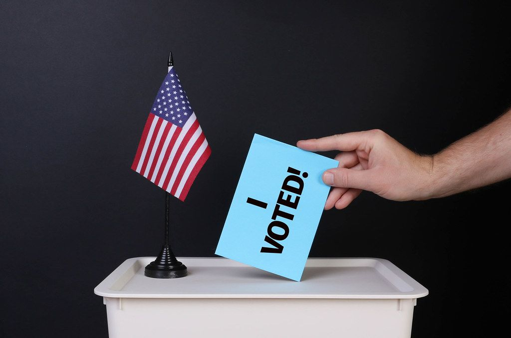 Voter holds blue envelope with I Voted! text