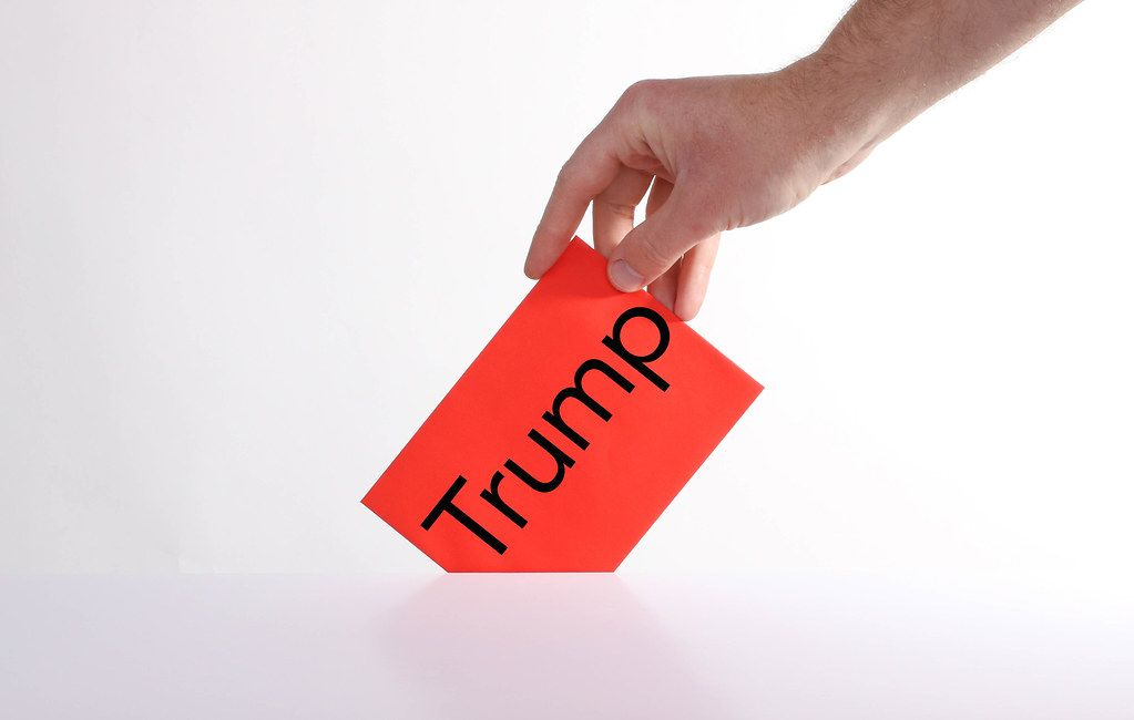 Voter holds red envelope in a hand with Trump text