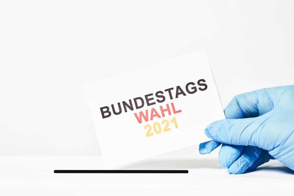 """Wahl und Corona: Hand mit Einmalhandschuh wirft Zettel mit Schrift """"Bundestagswahl 2021"""" in die Wahlurne ein"""