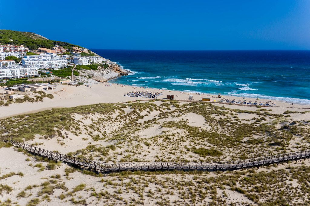 Walkway on the dunes with scanty vegetation by the beach of Cala Mesquida, Mallorca. Aerial view