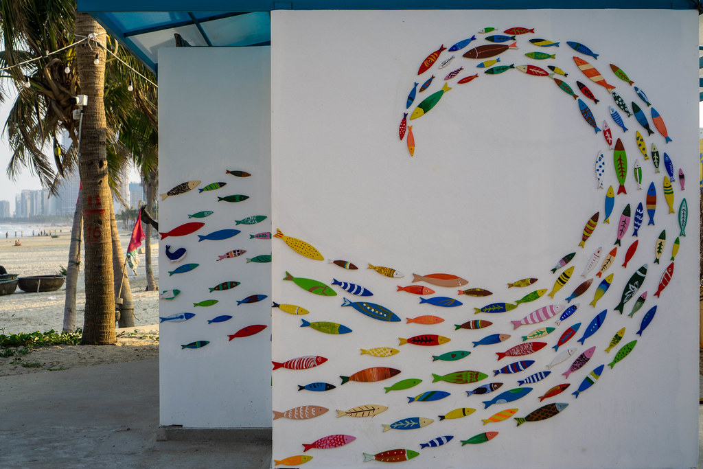Wall Art Wave made from Colorful Fish on a Public Toilet next to a Beach Bar at My Khe Beach with Palm Trees and Sand Beach in the Background in Da Nang, Vietnam