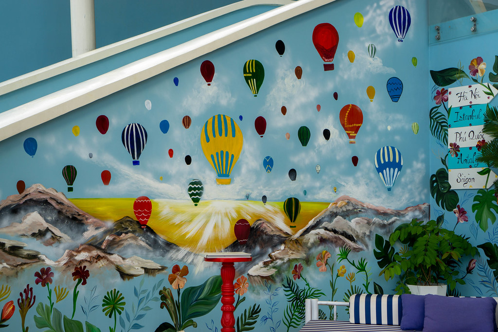 Wall Art with Colorful Hot Air Balloons, Mountains, Sunset and Plants on a Staircase Wall at Istanbul Beach Club in Phu Quoc, Vietnam