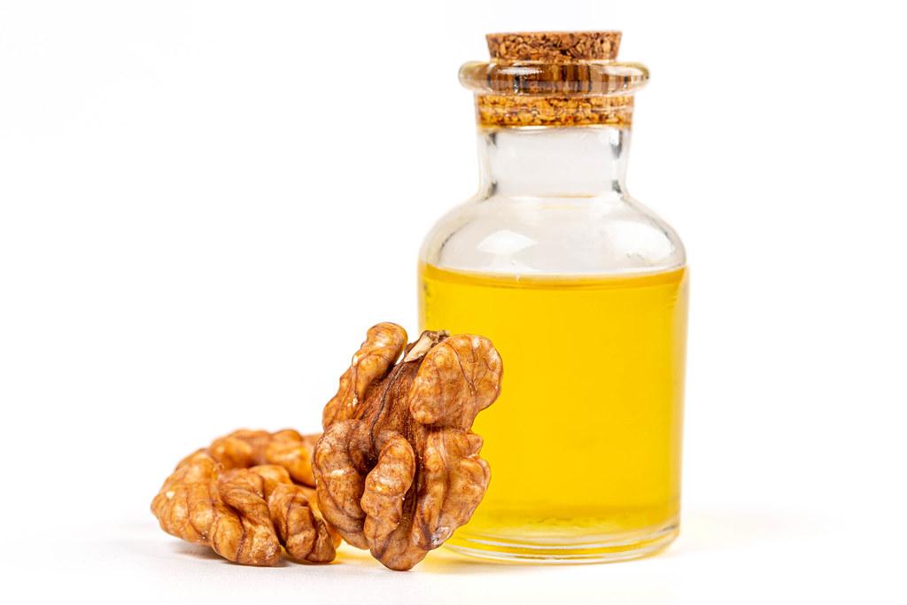 Walnut essential oil and fresh, unshelled walnuts