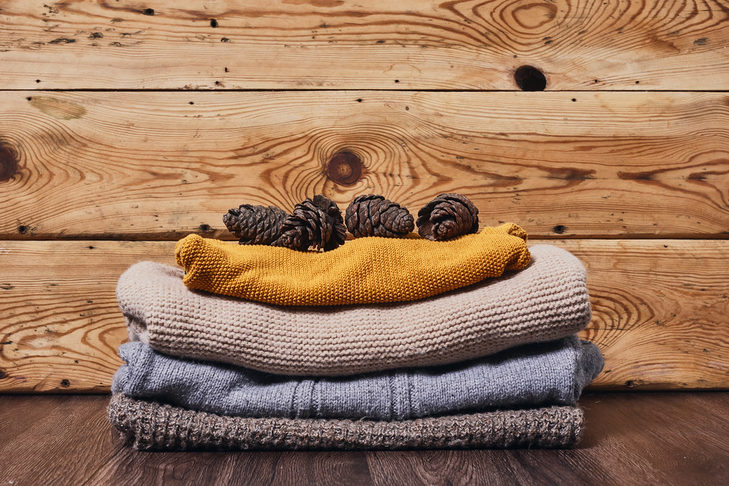 Warm sweaters and pine cones on wood