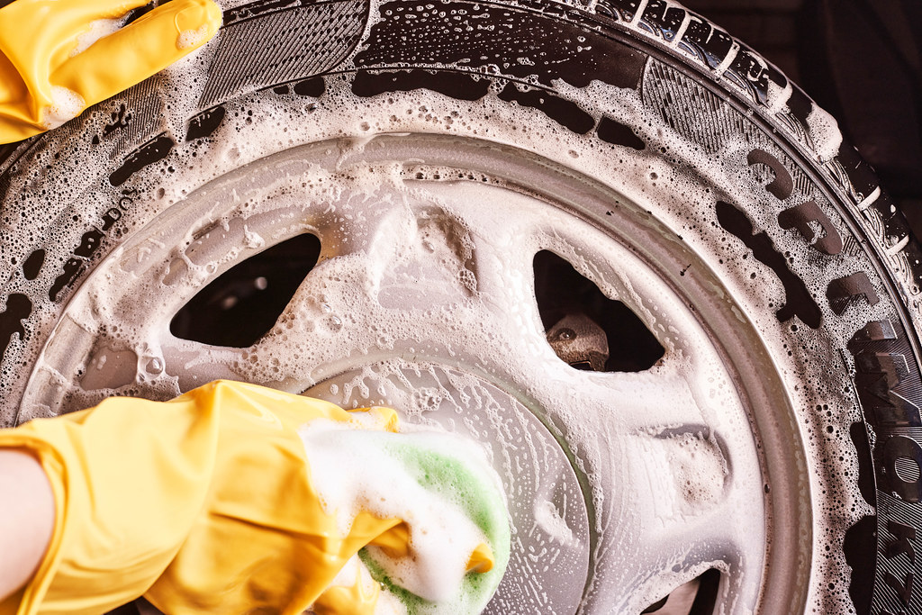 Washing car tires with a sponge