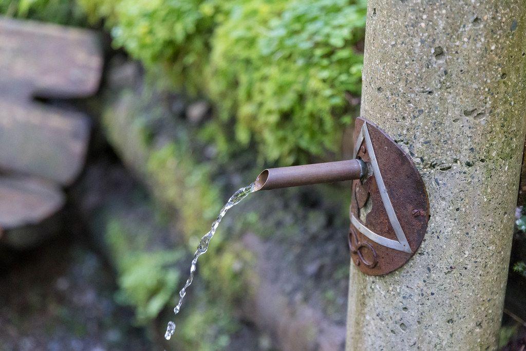 Wasser fließt aus einem Trinkbrunnen aus Stein und Metall im Grünen an dem Mühlbachweg in Alpbach