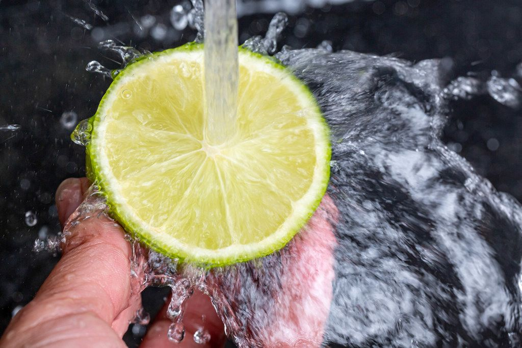 Water pours on half a ripe lime and splashes