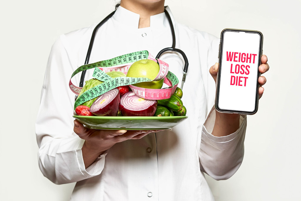 Weight loss diet - Doctor holds fresh fruits and vegetables and smartphone
