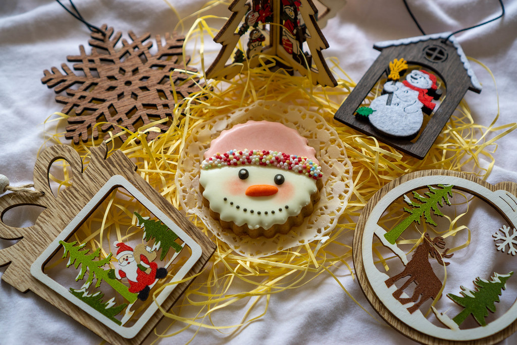 Weihnachts-Deko wie Weihnachtsbaum, Schneeflocke und Weihnachtsmann um ein Schneemann Gesicht als Lebkuchen Plätzchen mit Zuckerperlen und Zuckerguss Dekoration