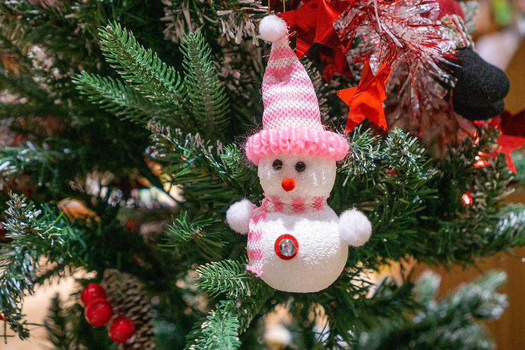 Weihnachtsbaum Dekoration im Schneemann-Design mit Mütze und Schal neben Sternen und Weihnachtsmann Nahaufnahme