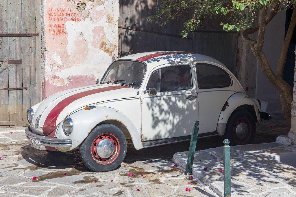 Weiß-roter Volkswagen Käfer Oldtimer in einer Gasse vom Dörfchen Chalki auf Naxos, Griechenland