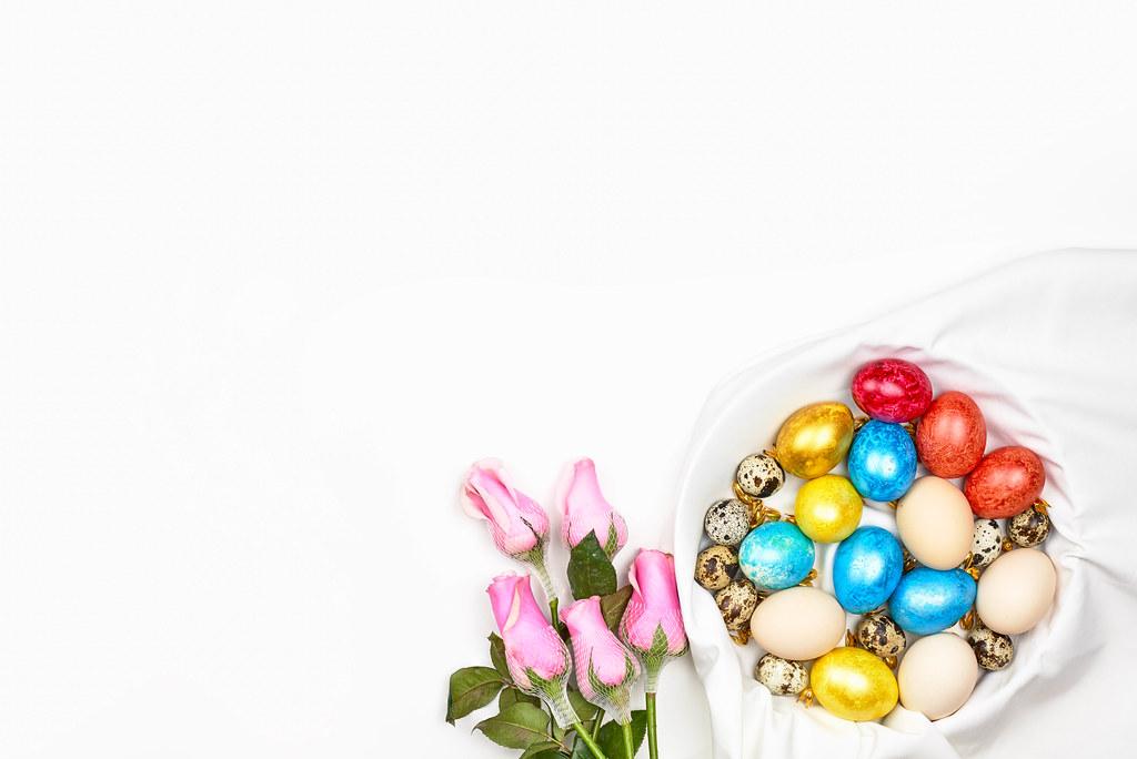 Weißer Ostern Hintergrund mit Platz für Text: bunte Eier, Wachteleier und Rosen