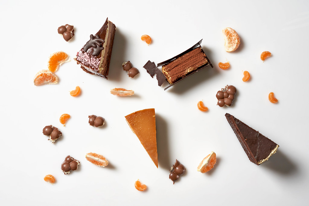 Weißer Patisserie-Hintergrund mit vier Tortenstücken und Orangen- und Mandarinenstücken