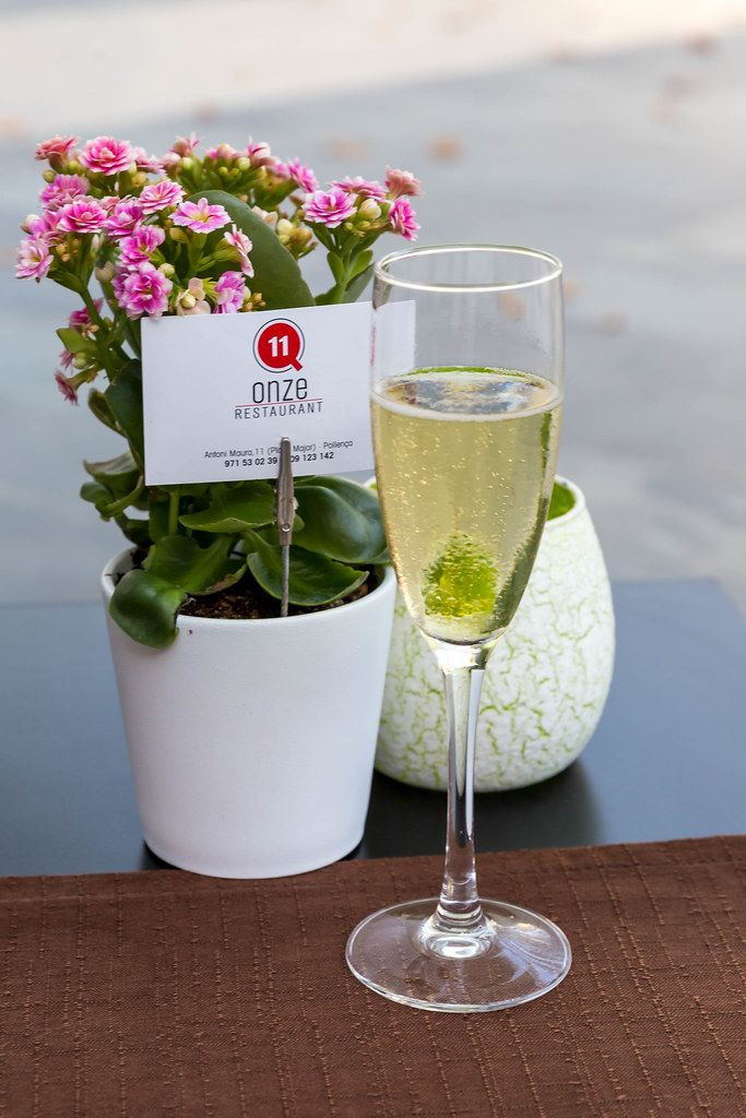 Welcome glass of prosecco and pot of flowers on the table at restaurant Q11 in Pollença, Mallorca