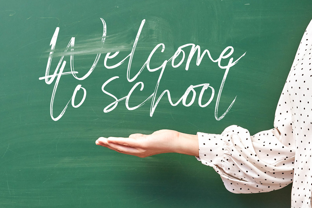 Welcome to school - a teacher welcoming pupils