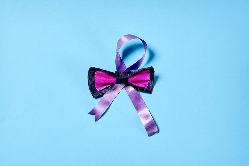 Weltkrebstag am 4. Februar: eine lila Schleife mit rosa-schwarzer Fliege vor blauem Hintergrund