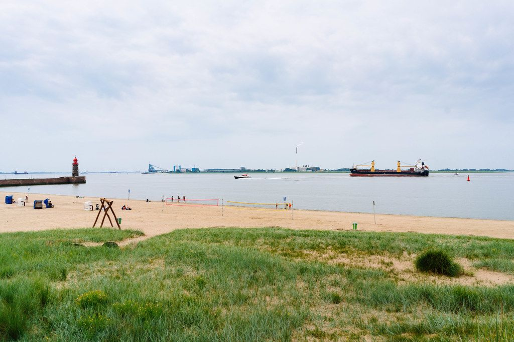 Weser sand beach with lighthouse and big tanker ship in the water
