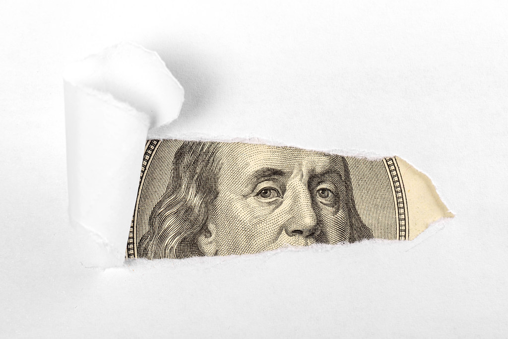 White background, from under which a portrait depicted on a hundred dollar bill peeps