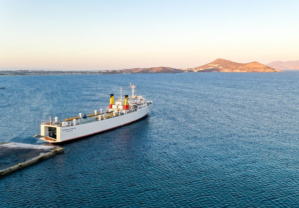 White cargo ship Kapetan Christos in the waters of Naxos, Cyclades, Greece, in sunset light. Drone shot