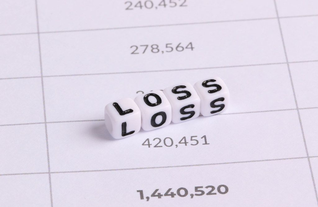 White cubes with Loss letters on financial document