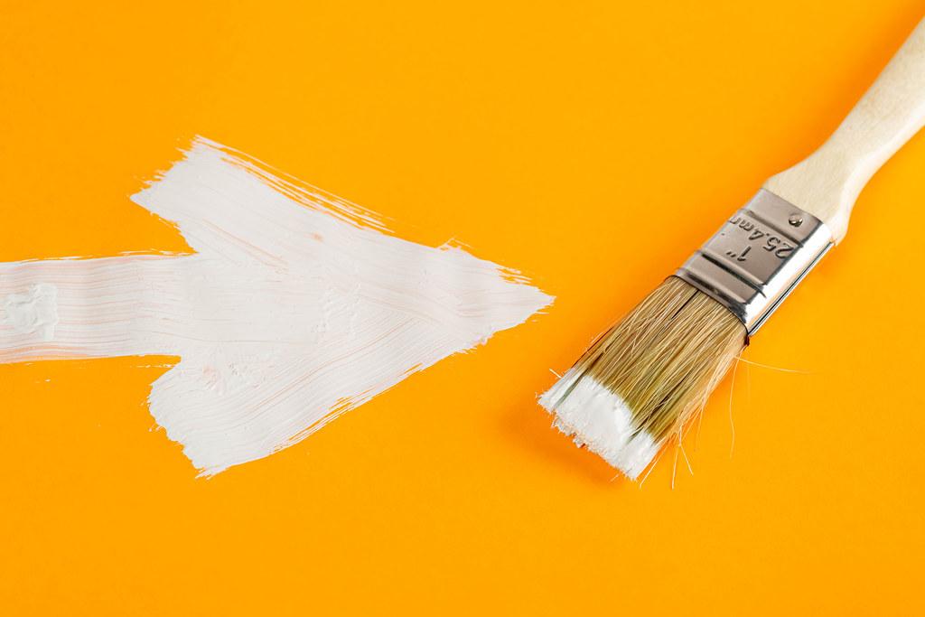 White drawn arrow on orange background