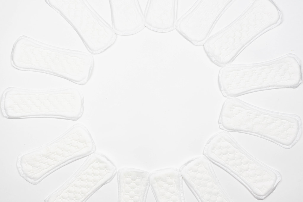 White feminine pads placed in circle form on white background